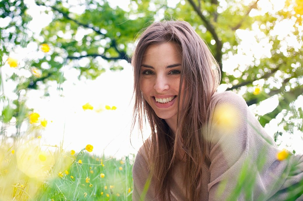 Adult woman smiling as she lays on the grass with the sun shining